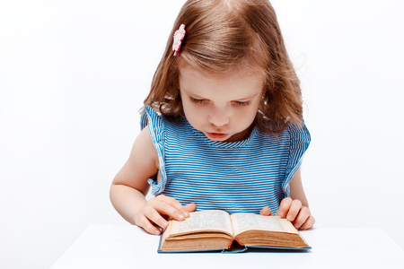 book jacket: Little girl of preschool age in a blue jacket, curly hair, hairpin, open mouth, reads the small book while sitting at table. white background. isolate. Stock Photo