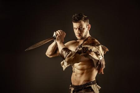 gladius: Portrait of handsome muscular gladiator with sword. Isolated. Studio shot. Black background