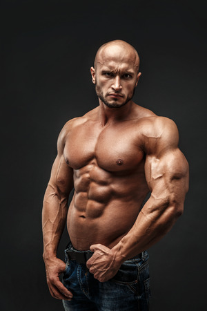 tough guy: Shirtless muscled fitness man. Cool looking. Tough guy. Bald. Tanned skin. Studio shot on black background.