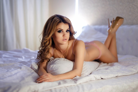 Beautiful young woman wearing lingerie lying in bed. Selective focus.