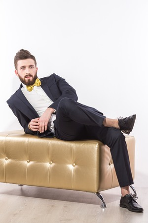 pouffe: Portrait of handsome man relaxing on modern pouffe in elegant suit with bow-tie
