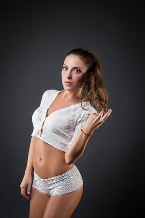 white pants: Side view of sexy brunette in white pants posing against of grey background.Studio shot