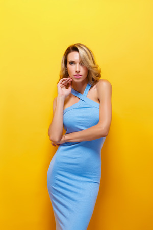 blue dress: Portrait of attractive young model with blonde hair wearing blue dress against of yellow background.Isolated Stock Photo