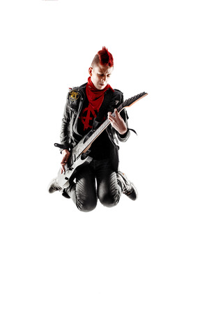 mohawk: Wild teen boy with red haired mohawk playing guitar while jumping. Isolated