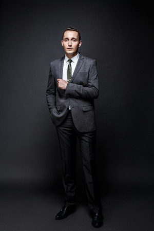 expressive face: Serious business man brown hair with expressive face wearing grey suit and tie. Isolated on dark background. Stock Photo