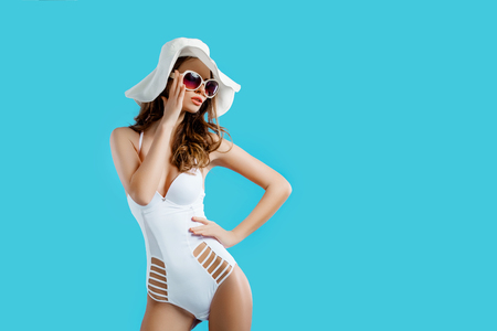 etalon: Attractive girl in a white bikini, hat, sunglasses, emotionally opened mouth on a bright blue background with a perfect body. Isolated. Studio shot.