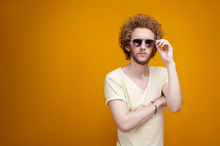 puzzlement: Portrait of curly-haired young man in sunglasses looking confused at camera.Isolate.Yellow background.