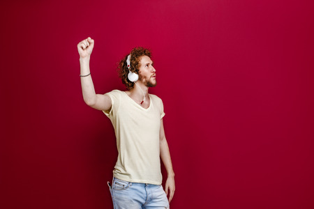 Portrait of young man in casual clothes listening to music via headphones with fist up. Red background. Isolate.