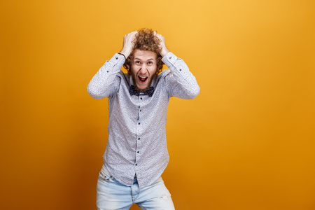 Portrait of male model tearing hair in hysteria on yellow background. Isolated. Big sale concept. Stock Photo