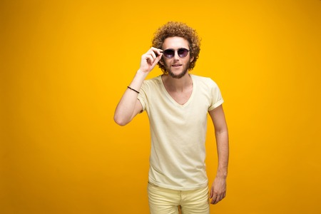 puzzlement: Portrait of curly-haired young man in sunglasses and bermudas looking confused at camera. Isolate. Yellow background.