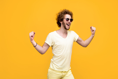 puzzlement: Portrait of curly-haired successed young man in sunglasses and bermudas hands up. Isolate. Yellow background.