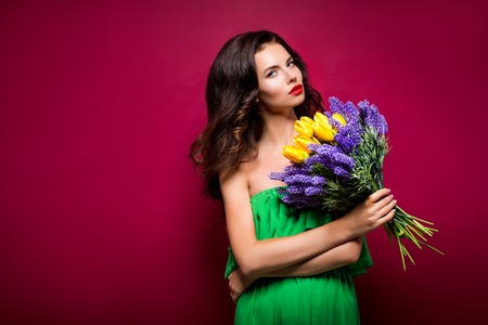 vinous: Long-haired seductive brunette with bouquet of flowers. Vinous background. Isolated Stock Photo