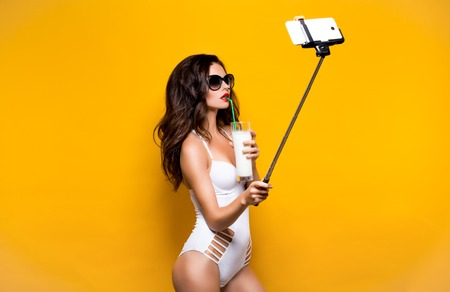 monokini: Beautiful brunette model in sunglasses and white monokini taking selfie with cell on selfiestick while drinking cocktail. Studio shot
