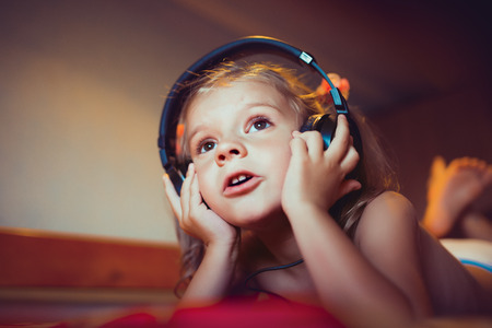 lifestyle looking lovely: Cute little kid listening music lying on bed at home