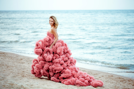 Beauties blonde young woman for long amazing white pink wedding sexy dress on the sea
