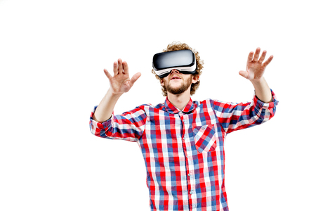 experiencing: Young curly-haired man in plaid shirt using a VR headset and experiencing virtual reality isolated on white background Stock Photo