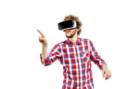 Young curly-haired man in plaid shirt using a VR headset and experiencing virtual reality isolated on white background 스톡 콘텐츠