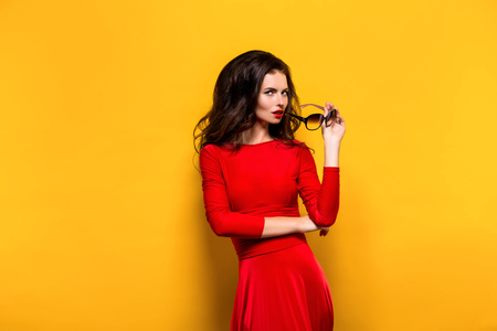 bright color: Portrait of beautiful elegant brunette with red lips wearing sunglasses and red dress. Isolated. Stock Photo