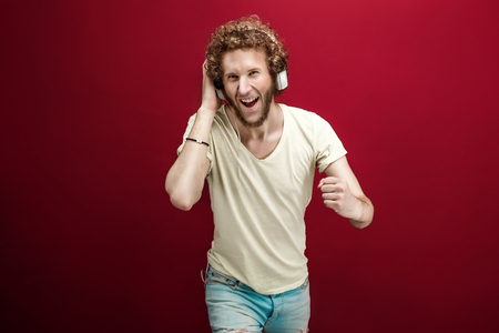 listen fist: Young man in casual clothes and headphones enjoying music. Studio shot.