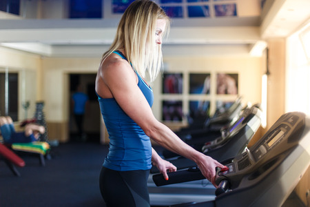 self conscious: Young woman at the gym exercising. Run on on a machine.