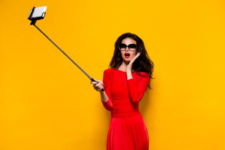 Portrait of beautiful brunette in awesome dress and red lips wearing sunglasses while making selfie with stick. Isolated Stockfoto