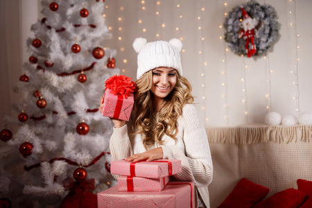 fur tree: Portrait of cheerful beautiful woman in white hat and sweater with Christmas presents in decorated room with white fur tree.