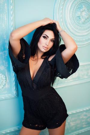 Portret van aantrekkelijke sexy vrouw in zwarte overall op de blauwe, groene achtergrond