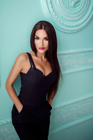 overall: Portrait of attractive sexy woman in black overall with hand in pocket on blue background