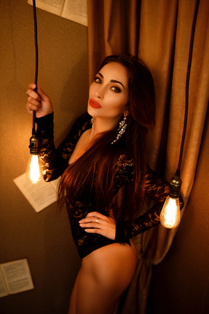 thin bulb: Portrait of beautiful brunette woman posing in black lace body with illuminated electric lamps hanging on wires