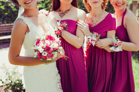 Row of bridesmaids with flowers on hands, holding each other