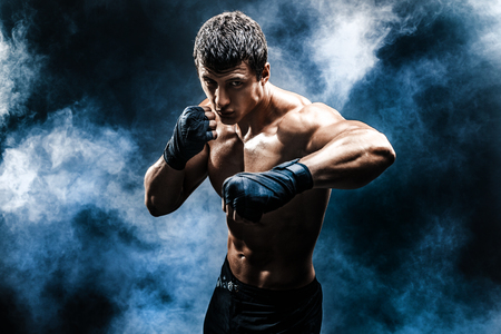 Muscular kickbox or muay thai fighter punching in smoke.