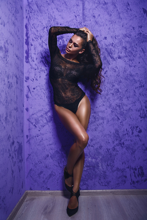 ojos negros: Portrait of sensual young brunette model in bra and lace body posing with eyes closed on bright violet background.