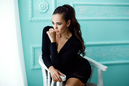 overall: Portrait of attractive sexy woman in black overall on blue background Stock Photo