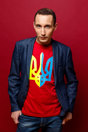 blazon: Portrait of confident young man wearing jacket and t-shirt with print of Ukrainian blazon in national colors