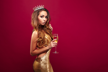 joyas de oro: Portrait of young adorable girl wearing golden dress and crown with gems posing with glass of champagne on red background