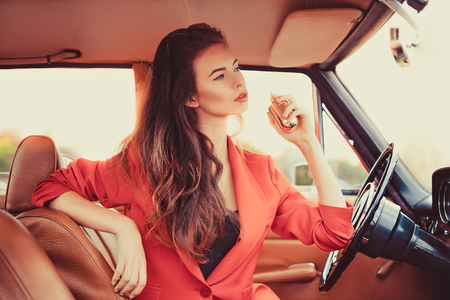 Beautiful young woman sitting behind the wheel in retro automobile using a perfume