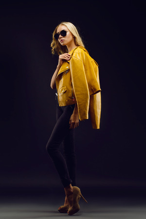 full lenght: Beautiful, tall, slim fashion model in yellow jacket posing on black background full lenght. Stock Photo
