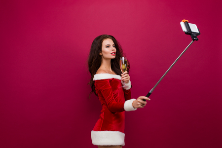 decollete: Sexy brunette woman in red christmas dress with glass of champagne in one hand, holding selfie stick in other hand, and taking self portrait. Isolate.