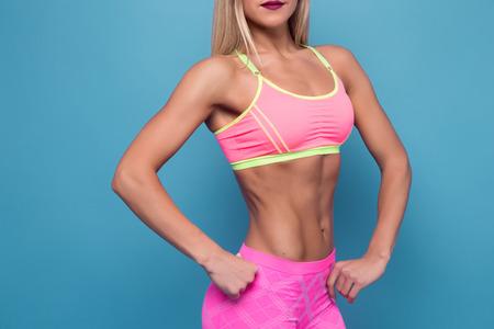 flat stomach: Colorido de la rubia culturista adulto joven chica sexy con el pelo largo Retrato de mujer de corte delgado deportivo muy caliente que se opone a azul. Espacio de la copia. vientre plano con la prensa