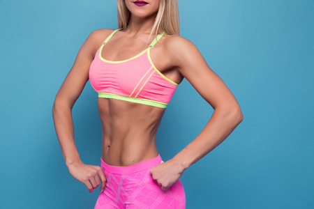 flat stomach: Colorful of blonde bodybuilder young adult sexy girl with long hair Portrait of slim sporty cut VERY HOT woman standing against blue. Copy space. Flat stomach with press Foto de archivo