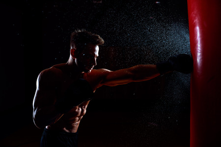 Young male boxer hitting punching bag on black background.