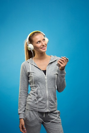 staying fit: Beautiful blond fit caucasian lady in grey sport  with headphones listening music. Isolated on blue background.