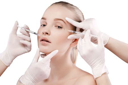 beautycare: Portrait of young blonde woman taking care of her face skin with botox syringes. Isolate on white.