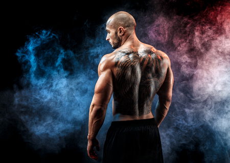 Bald unrecognizable tattooed man with strong muscles posing, resting in smoke. Looking sideways