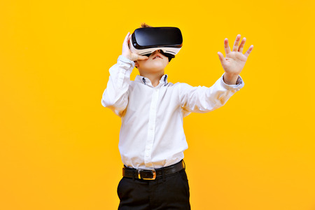 Kid in formal outfit wearing VR glasses putting hands out in excitement isolated on orange background. Stock Photo