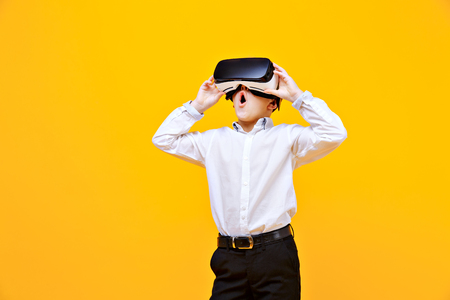 Kid in formal outfit wearing VR glasses putting hands out in excitement isolated on orange background. Standard-Bild