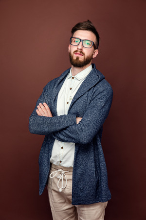 Studio shot of young male in casual outfit posing on brown background and crossed his arms.