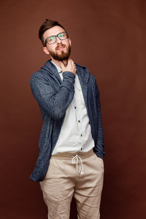 Studio shot of young male in casual outfit posing on brown background and holding hand on neck.
