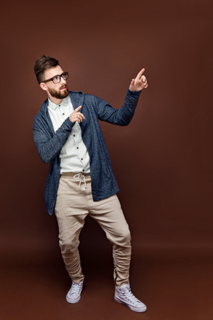 Studio shot of young male in casual outfit posing on brown background with arms to the side
