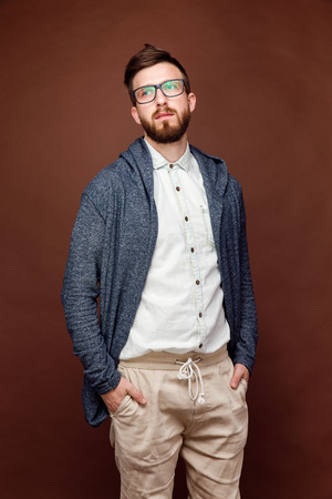 Studio shot of young male in casual outfit posing on brown background and holding hands in a pocket.
